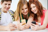 education, relationships and technology concept - three smiling students with smartphone at school