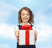 people, childhood, summer and holidays concept - happy smiling girl with gift box over blue sky background