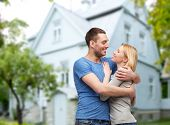 love, people, real estate, home and family concept - smiling couple hugging over house background