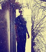 Abstract soft focused duotoned double exposure portrait of man in a doorway and black forest toned with a retro vintage instagram filter