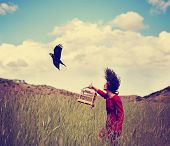 a girl walking in a wheat field on a warm summer day with a black bird toned with a retro vintage instagram filter