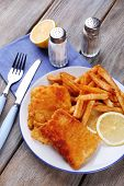 Breaded fried fish fillets and potatoes with with sliced lemon and cutlery on plate and wooden planks background