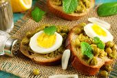 Sandwiches with green peas paste and boiled egg on burlap cloth on color wooden background