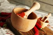 Ground red pepper in mortar with chili pepper on wooden background
