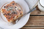 Homemade pie with jam and glass of milk on napkin and wooden planks background
