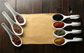 Different kinds of spices in ceramics spoons on blank paper sheet on wooden background