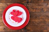Cookies in form of heart in plate on rustic wooden planks background