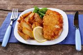 Breaded fried fish fillet and potatoes with asparagus and lemon on plate and wooden planks background