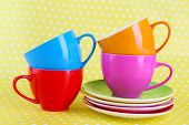 Colorful cups and saucers on color background