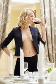 Pretty topless blonde drinking wine in restaurant