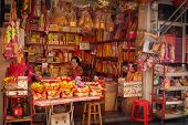 Malaysia, Penang, Georgetown - Circa Jul 2014: Elderly Woman Selling Fireworks From A Vendor's Stall