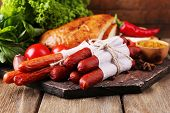 Assortment of thin sausages, bread, mustard in bowl and spices on cutting board, on wooden background