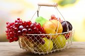 Assortment of juicy fruits in wicker basket on table, on bright background