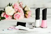 French manicure set with white tip polish, dividers and top coat shine applicator for nails on color wooden background