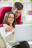 Young couple relaxing on sofa with laptop in the living room.Selective focus