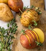 Sliced raw potatoes with sprigs of thyme, sea salt and butter before baking