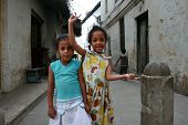Two Little Black Arab Girl Standing On A Narrow Street.