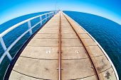 Pier in blue ocean water with fisheye horison. Basselton jetty