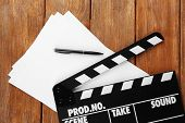 Movie clapper with sheets of paper and pen on wooden planks background