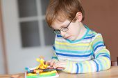 picture of little kids  - Little boy adorable creative kid boy with glasses playing with dough colorful modeling compound sitting at table at home or in school room. Creative leisure with kids.