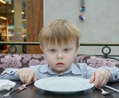 Blond Boy Sitting At A Table With An Empty Plate