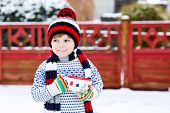 stock photo of cold drink  - Little boy drinking chocolate drink with marshmallows outdoors with snow background - JPG
