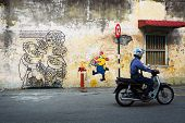 Malaysia, Penang, Georgetown - Circa Jul 2014: Man On A Motorcycle, Passing Two Diverse Murals Paint