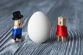 Easter Concept. Romantic Couple. Man, Woman And White Easter Egg. Clothespins. (soft Focus)