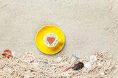 Cup And Net With Shells On Sand