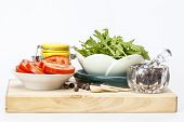 Black pepper in a transparent mortar with a pestle, tomato slices, leaves of arugula and multi-color