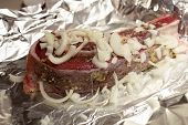 picture of brisket  - Raw brisket of beef with onions on a foil - JPG