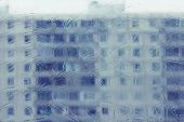 Condominium view through window with melted frost patterns. Shallow DOF, focus on the frost patterns