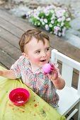 Happy Boy Holds Up His Pink Dyed Easter Egg