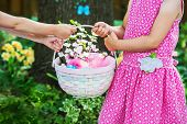 Two Girls Holding An Easter Basket With Flowers