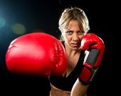 Young Fit And Strong Attractive Boxer Girl With Red Boxing Gloves Fighting Throwing Aggressive Punch