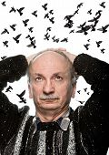 stock photo of 55-60 years old  - mature man looking up on sky with flying birds - JPG