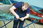 Automobile glazier works with windscreen or windshield of a car in auto service station garage before installation