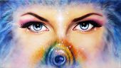pic of  eyes  - A pair of beautiful blue women eyes looking up mysteriously from behind a small rainbow colored peacock feather - JPG