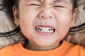 pic of teeth  - close up of a childs face in pain from a tooth - JPG