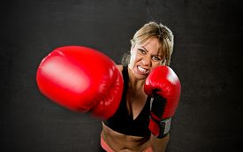 foto of boxers  - young fit and strong sexy boxer girl with red boxing gloves fighting throwing aggressive punch training workout in gym feeling angry isolated on black background - JPG
