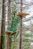 stock photo of roping  - Wood platforms and rope netting on a challenging ropes course high in the pines - JPG