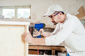 image of workplace safety  - Carpenter working assembling a drawer with a screwdriver - JPG
