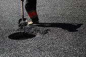 image of manhole  - Urban road under construction asphalting in progress worker with a shovel near sewer manhole - JPG