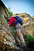 picture of cliffs  - young climber with backpack climbing up a cliff - JPG