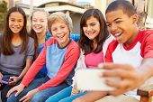 stock photo of pre-adolescent child  - Group Of Children Sitting On Bench In Mall Taking Selfie - JPG