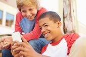 foto of tweeny  - Two Teenage Boys Reading Text On Mobile Phone - JPG