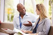 stock photo of tutor  - Two College Tutors Having Discussion Together - JPG