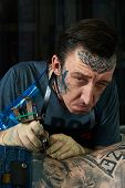 image of freaky  - Closeup portrait of freaky tattoo master in his studio - JPG