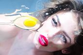 picture of human egg  - Adorable pretty cute girl with curly hair big beautiful eyes and bright pink lips looking through the flat glass surface with raw yellow yolk and white of an egg on blue background horizontal picture - JPG