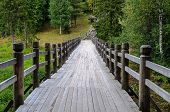 stock photo of ravines  - Long wooden footbridge with handrails over the ravine in forest summer time - JPG